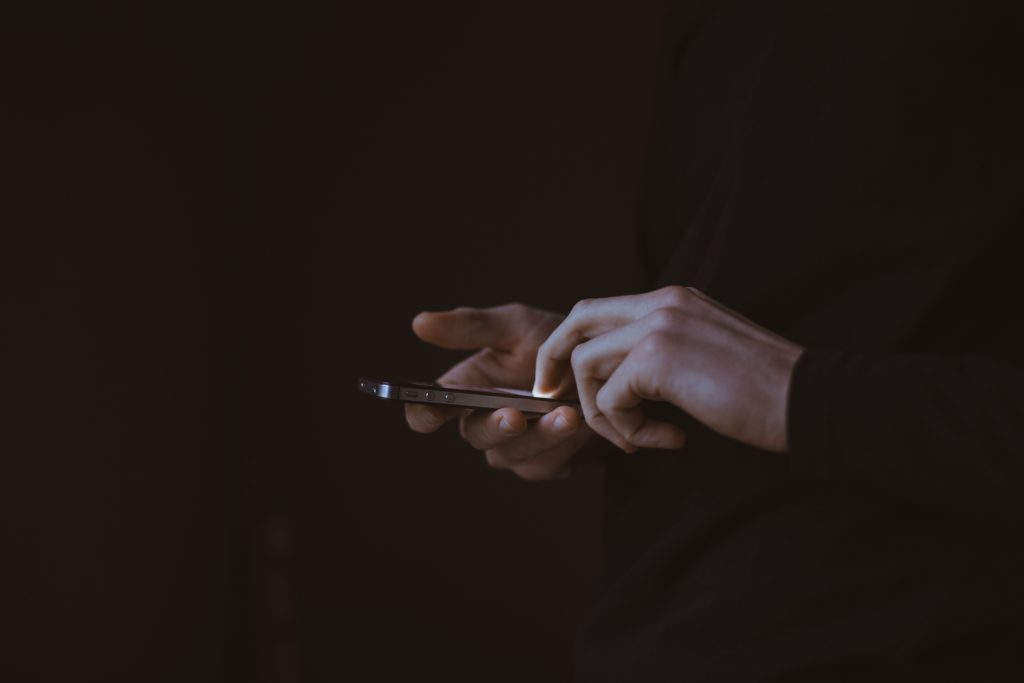 Hands isolated in darkness using smartphone